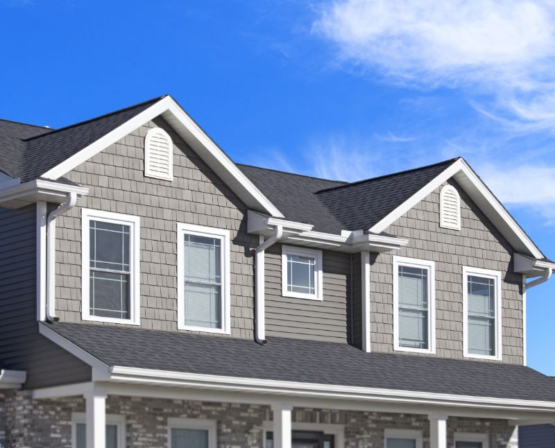 roof and gutters of a home with gray siding